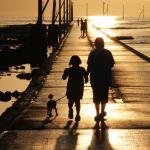 夕陽に向かって散歩する家族連れ。映画のシーンのようだ。