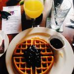 My mimosa in a wine glass and waffles with blueberry compote