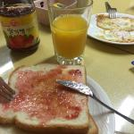 Breakfast with toast, jam/butter, orange juice/coffee, sunnyside up