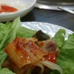 Kimchi on top of samgeopsal in lettuce leaf