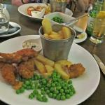 Chicken Goujons, chunky chips in basket and garden peas.