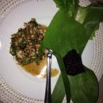Laap kai with its black sticky rice in a banana tree leave.