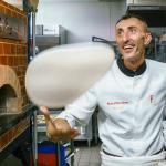 Pizzaiolo juggling with Pizza dough