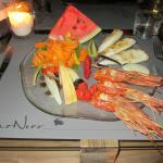 Grigliata di gamberoni e calamari con appetitoso mix di frutta e verdura.