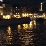 Romantic walk on the Pont Neuf bridge on the Seine with the lights of the Eiffel Tower in the di