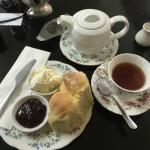 Devonshire tea with delicious scones and tea in china cups