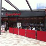 The front entrance to Frankie and Benny's with outdoor seating.