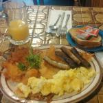 Orange juice, potato hash, scrambled eggs, sausages, and toast.  Mmm-mmm.