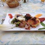 Entrée savoureuse avec un manchon de canard, une pomme de terre avec du fromage, une tartine de