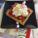 Waffle with strawberries, marshmallows, whipped cream and golden syrup