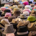 Hats on sale in three different booths.