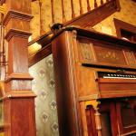 The pump organ sits beside the bannister to the upper level where the rooms are located