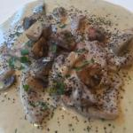 Veal with a cream white wine and mushroom sauce with a dish of fresh vegetables