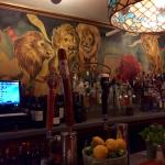 Behind the bar (note, the 'red lion') ;-)