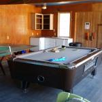 Games room with busted ping pong table and garbage on the pool table