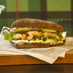 A sandwich with salmon fish, prepared with brown bun, milk paste and fresh cucumbers