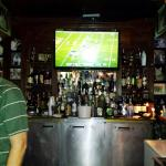 Jump behind the bar; watching the Packers on TV.