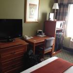 Blick auf TV, Schreibtisch und Kühlschrank mit Mikrowelle