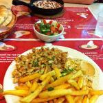 Shawarma with hummus and fries (front), a small Israelian salad (middle) and Shashuka (back).
