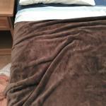 Ducha sucia, suelo bajo mesita con cosas, suciedad en grifo y cama mal hecha al quitar la colcha