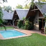 View across lawns and pool to the Leopard Cottage and lapa.