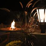 An outdoor fireplace with Adirondack chairs