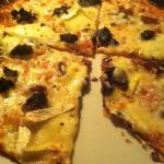 Pizza de morcilla, ceba caramelitzada, pinyons i brie