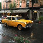 Film shoot in the neighborhood, old taxi passing by Building on bond.