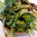 Quiche with greens atop.