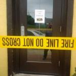 Close-up of Fire Marshal tape at side door and notice of closure.