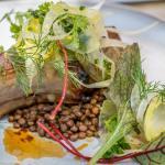 Pork chop served with lentils and garden vegetables