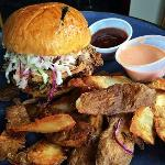 Pork Sanwich topped with coleslaw on a Brioche bun with Fried Potato Skins