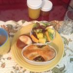 Breakfast with baked eggs and veggie, roll, orange marmalade, mixed fruits, and orange juice.