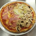 Quattro Stagioni - Tomato Base,  Mozzarella Cheese,  Mushrooms,  Anchovies,  Ham, Artichokes.