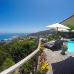 Deck, heated pool, lounge chairs all overlooking Camps Bay