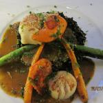 Grilled scallops over squid ink risotto with asparagus and carrot