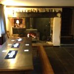 A Large eating table next to a warm fire