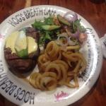 Steak with avocado, Hollandaise sauce, curly fries and salad garnish