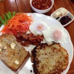 Fruit muesli and hash browns poached eggs bacon baked beans and toast