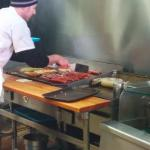 View of the hot dogs being split and cooked on the hot plate