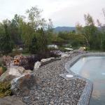 Bassin d'eau chaude, salon extérieur autour du feu et, au fond, l'étang.