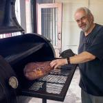 Pit Master Werner Jayson prepares a beef brisket in the wood smoker.
