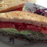 Marinated portobello sandwich on whole grain bread with avocado, sprouts and tomato.