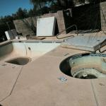 The pool with old thrown out mattresses and air conditioning systems