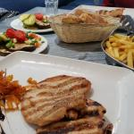 Grilled chicken breast with chips and side salad.