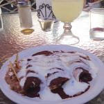 Enmoladas-tortillas stuffed with chicken smothered on mole sauce