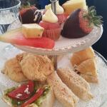 small servings 1 finger sandwich 1/3 croissant 1scone with jam and cream,slice of fruit, Bruchet