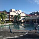 The big, round swimming pool is surrounded by the hotel rooms and villas.