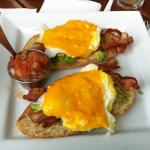Breakfast Tostada: Toast layered with crisp bacon, avocado, fried eggs, and cheddar cheese, topp