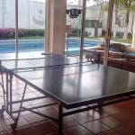 Table tennis, with the swimming pool and outside area on the background